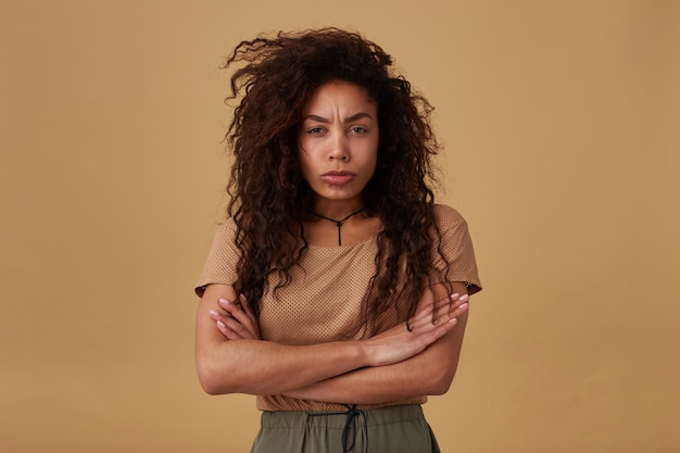 Offended young pretty curly dark skinned brunette lady folding her hands on chest while looking sadly and frowning her eyebrows, posing on beige