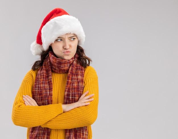 Offeso giovane ragazza slava con cappello da babbo natale e con sciarpa intorno al collo si erge con le braccia incrociate guardando il lato isolato sul muro bianco con spazio di copia