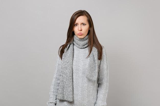 회색 스웨터를 입은 젊은 여성을 화나게 하고, 회색 벽 배경에 격리된 스카프를 삐죽 내밀고, 스튜디오 초상화. 건강한 패션 라이프스타일, 사람들의 진심 어린 감정, 추운 계절 개념. 복사 공간을 비웃습니다.