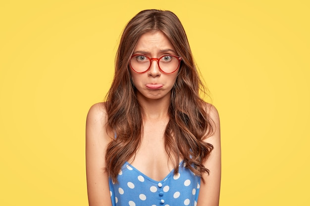 Offended young woman with glasses posing against the yellow wall