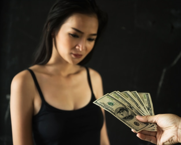 Offer us dollar money bills from buyer male hand to asian female sexy prostitute