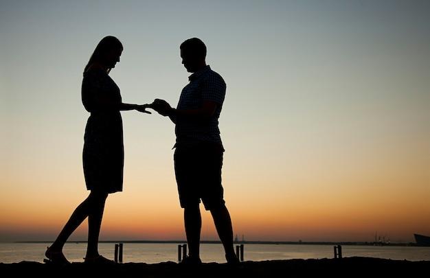 美しい夕日を背景にビーチであなたの手と心を提供し、婚約男は指輪を与え、女の子に結婚するように頼みます、彼女は幸せです