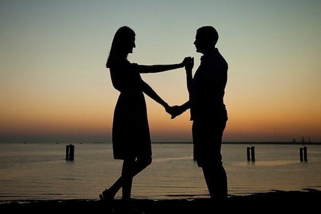 Offer your hand and heart on the beach against the background of a beautiful sunset, engagement a man gives a ring and asks a girl to get married, she is happy