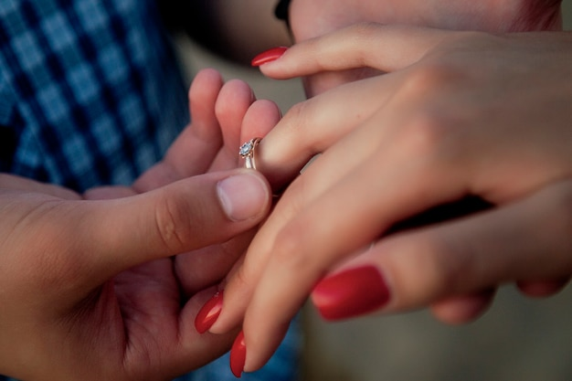 Offer your hand and heart, betrothal. close-up of male hand wearing a ring on a woman's hand. a man gives a ring and asks a girl to get married, she is happy.