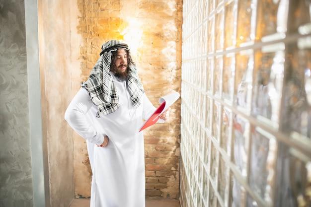 제안. 사무실에서 일하는 아라비아 사업가, 장치, 가제트를 사용하는 비즈니스 센터. 현대 사우디 라이프 스타일. 전통 의상과 스카프를 입은 남자는 자신감 있고 바쁘고 잘 생겼습니다. 민족, 금융.