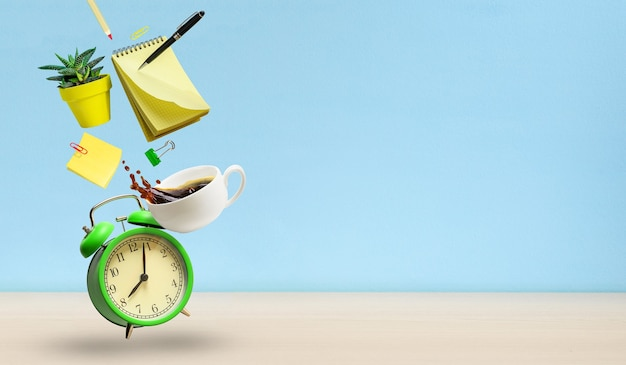 Office accessories notepad, alarm clock, coffee cup, plant flying over desk table on blue wall background. copy space