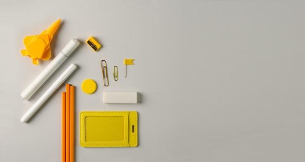 オフィスアクセサリーのペン、鉛筆、マーカー、ペーパークリップ、消しゴム、黄色の鉛筆削りは灰色の背景にあります。スペースコピーとセレクティブフォーカスで学校に戻るコンセプト Premium写真