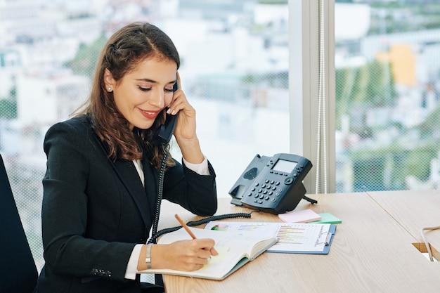 Администратор офиса разговаривает по телефону