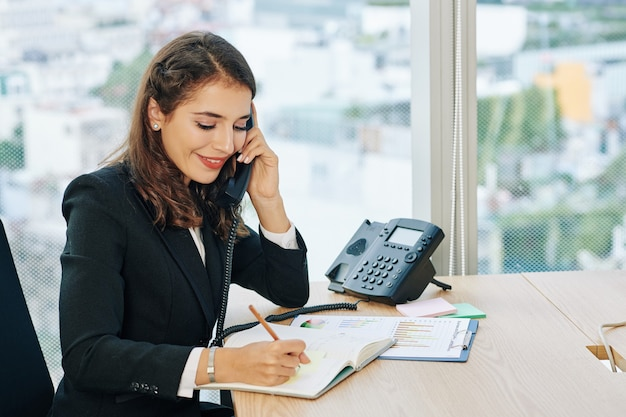 Office administrator talking on phone