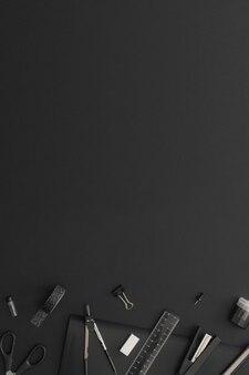 黒革の背景にオフィスや学校の文房具。学校に戻る