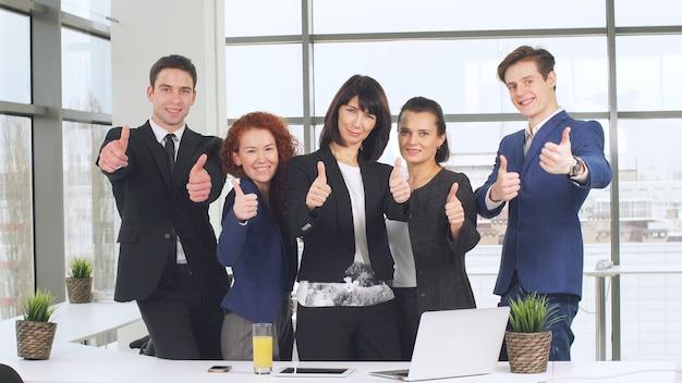 Концепция офиса и сыгранности, группа в составе бизнесмены имея встречу и показывая большие пальцы руки вверх.