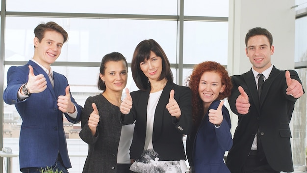 オフィスとチームワークの概念、会議と親指を現してビジネス人々のグループ。