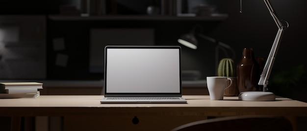 夜のオフィス暗い作業スペース空白の画面のラップトップは、テーブルランプからの光で木製の机をモックアップします