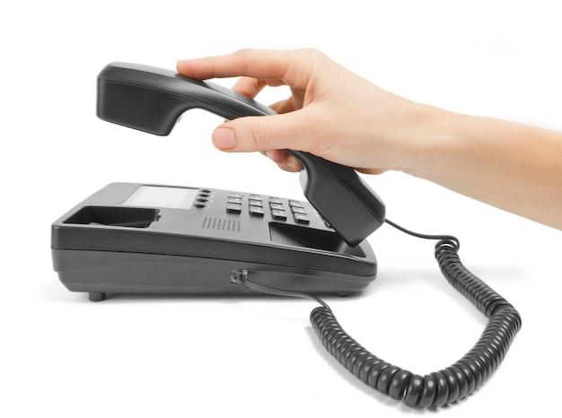 白で隔離の手とオフィスの黒い電話