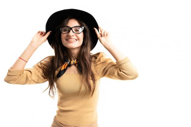 Офисная брюнетка модель с очками, шляпой и шейным платком позирует на белой стене