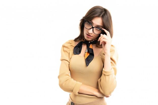 Офисная брюнетка модель в очках позирует на белой стене