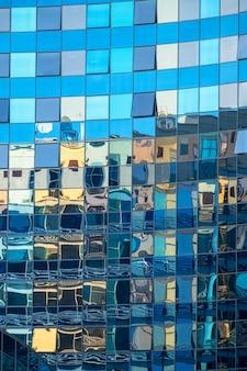 Офисное здание отражается в стеклянном фасаде другого офисного здания