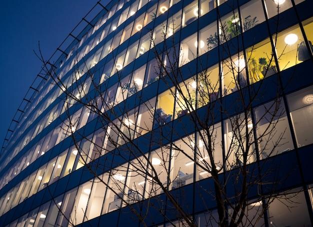 Office building windows at night on dark blue sky background