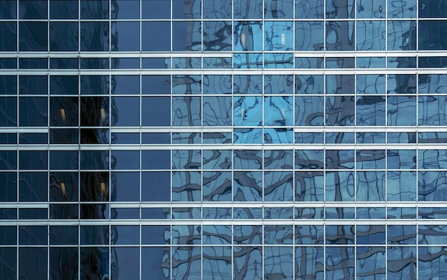 ビジネスの背景、ビジネスセンターの一般的なファサード、正面図の青いガラスのオフィスビルの窓のテクスチャ