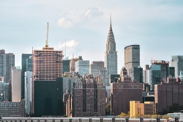 일몰에 스카이 라인에 사무실 건물 및 아파트. 부동산 및 여행 개념. 맨해튼, 뉴욕, 미국.