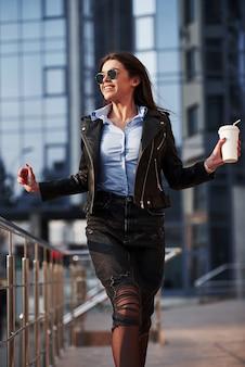Офисные здания позади. молодая красивая девушка в теплой одежде прогуливается по городу в выходные дни