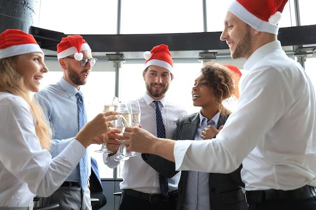 職場で一緒に冬休みを祝い、オフィスでシャンパンを飲むオフィスビジネスの同僚。メリークリスマス、そしてハッピーニューイヤー。