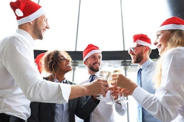 Коллеги по офисному бизнесу вместе празднуют зимние праздники на работе и пьют шампанское в офисе. веселого рождества и счастливого нового года.