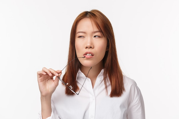 Office, business and lifestyle concept. close-up portrait of suspicious and thoughtful young businesswoman taking off glasses, biting its rim and squinting pondering while thinking,