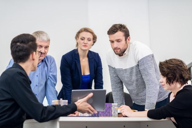 Офисная деловая встреча. команда сидит за столом в светящемся белом открытом пространстве. молодые работники представляют свой проект старшему седому боссу