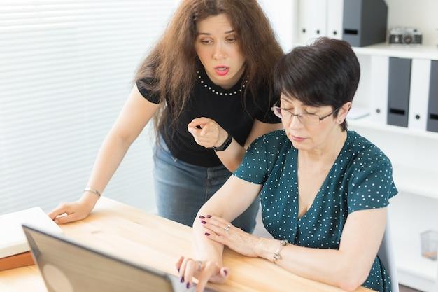 사무실, 사업가, 그래픽 디자이너 개념 - 여성들은 사무실에서 노트북으로 문제를 논의하고 있습니다.