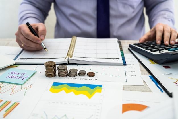 사무실 사업가 작업 및 동전을 사용하여 차트 및 문서를 사용하여 회사 이익을 분석합니다. 비즈니스 분석 및 전략 개념