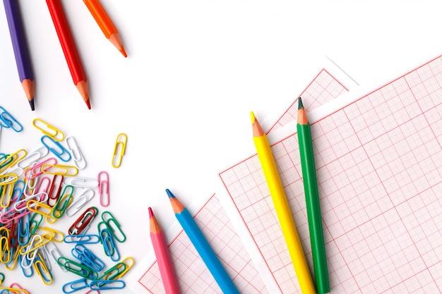 Офисный клип и цветные карандаши на белом фоне