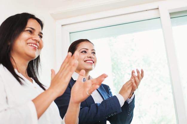 Коллеги по офису аплодируют успеху компании