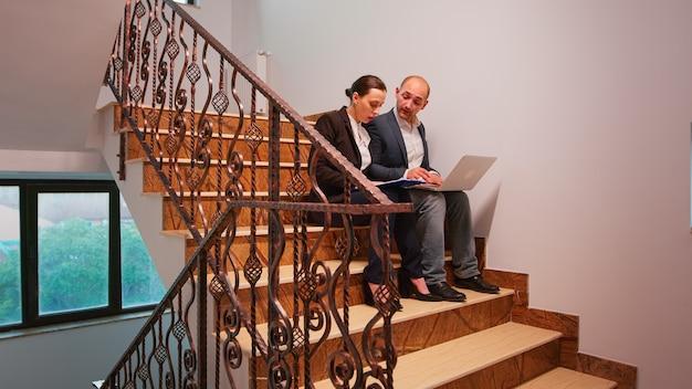 ラップトップで入力する企業の会社の建物の階段に座っている困難な締め切りの財務プロジェクトでのコワーキングを支援するオフィスの同僚。金融の職場を歩いているビジネスマンのグループ。