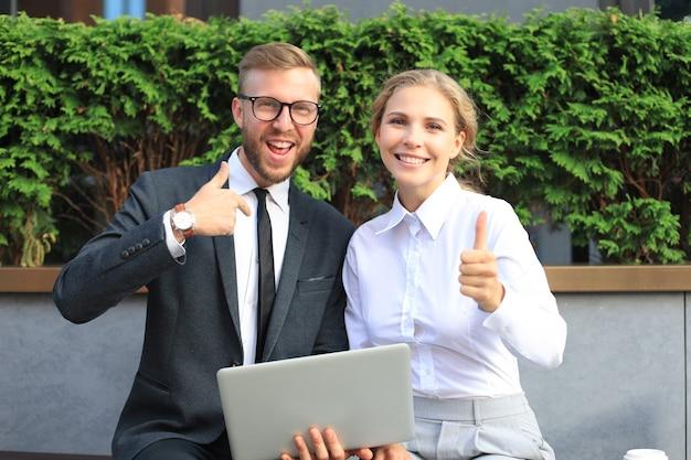 Коллеги в офисе, используя портативный компьютер и показывая пальцы вверх, сидя на скамейке на открытом воздухе.