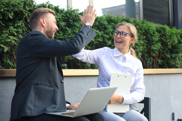 Office colleagues using laptop computer and giving five while sitting on a bench outdoor.
