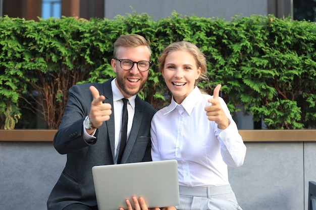 Office colleagues using laptop computer and showing thumbs up while sitting on a bench outdoor.