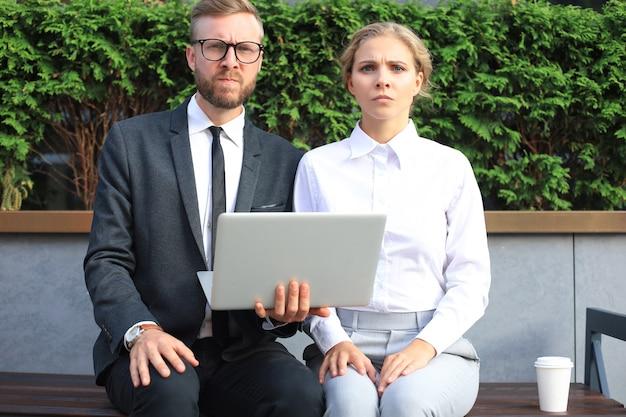 Коллеги в офисе с помощью портативного компьютера, сидя на скамейке на открытом воздухе.