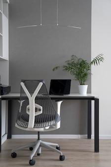 モダンなデスク、整形外科用の椅子、最新のコンピューター、テーブルの上に緑の植木鉢があるオフィスコーナー。