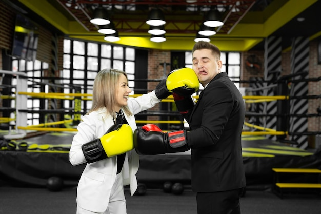 Office couple in boxing gloves wrestle in the ring.
