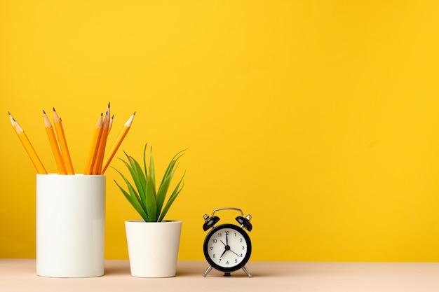 연필과 노란색 배경 전면보기에 대 한 편지지와 사무실 컵