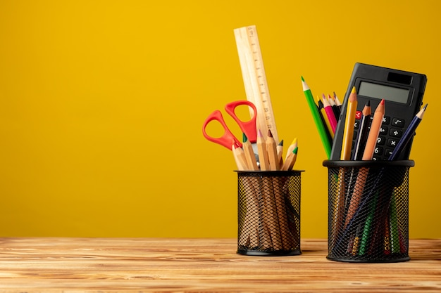 Офисная чашка с карандашами и канцелярскими принадлежностями на желтом фоне, вид спереди