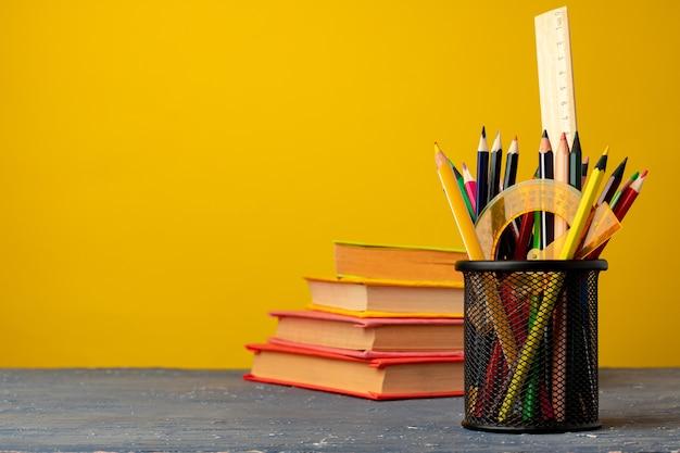 Офисная чашка с карандашами и канцелярскими принадлежностями на желтом фоне