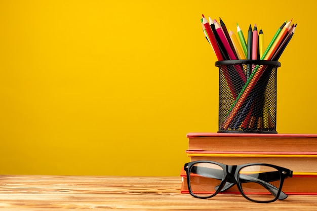 Office cup with pencils and stationery against yellow background