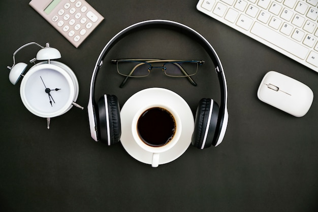 Office desk business objects of white coffee cup, keyboard, headphone, white alarm clock, calculator, mouse and glasses on blackboard
