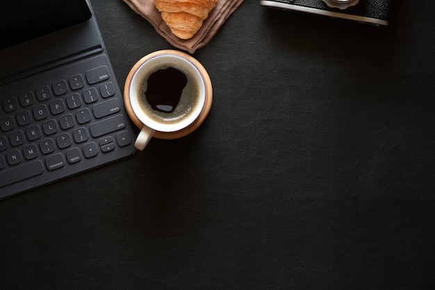 Office desk dark leather workspace with black cup of coffee, office supplies and copy space