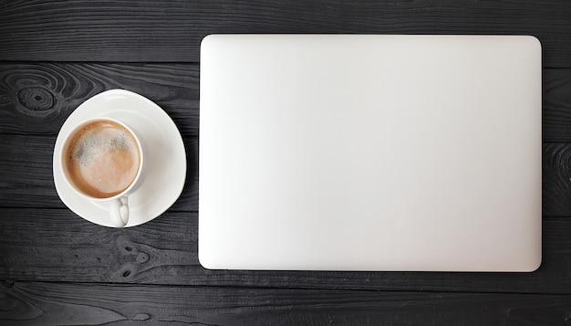 Стол офиса - портативный компьютер и кофейная чашка на деревянной текстуре и предпосылка с космосом экземпляра.