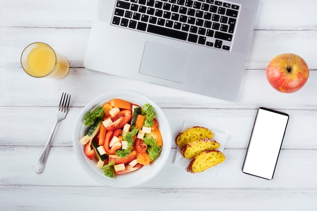 Office desk and laptop with healthy food