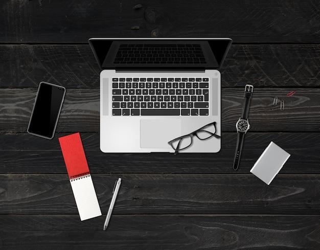 Вид сверху макета офисного стола, изолированные на черном деревянном фоне