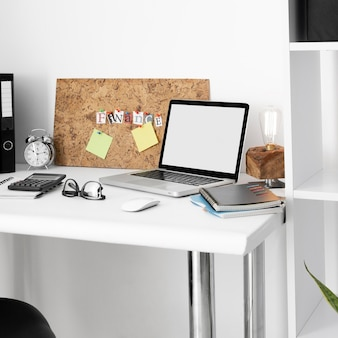 Office desk surface with laptop and notebooks